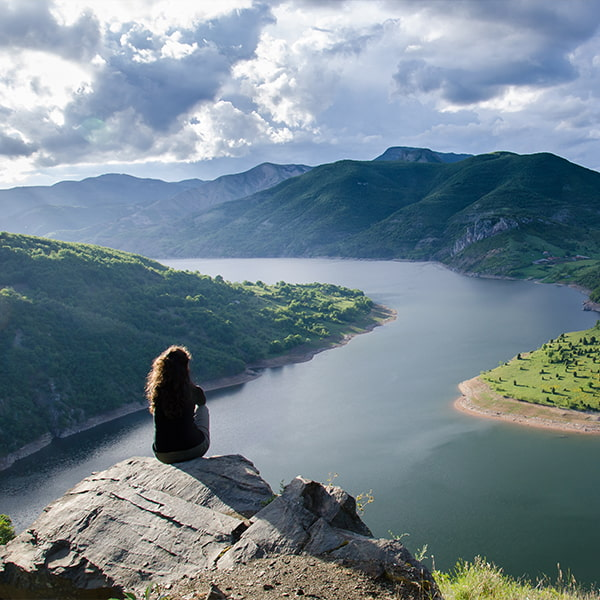 Woman sat on the top of a mountain looking across a lake