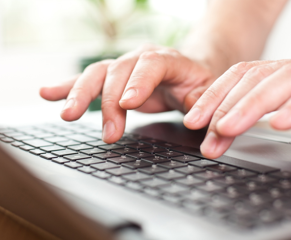 Man's hands typing on a laptop